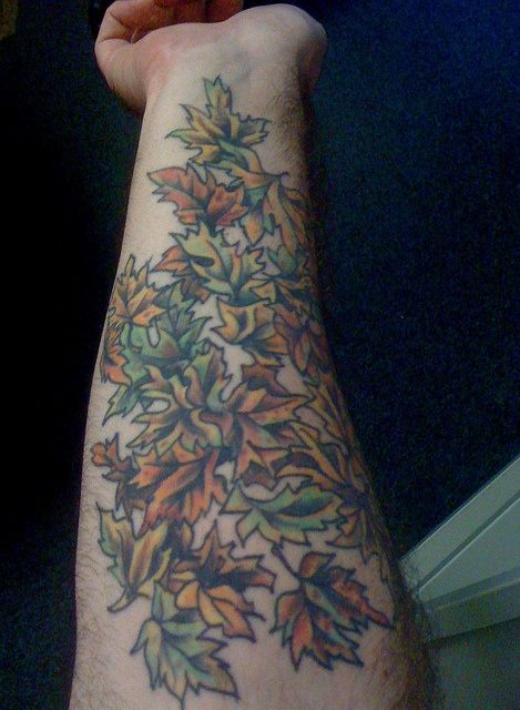 multicolored autumn leaves tattoo on arm