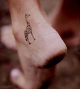small giraffe tattoo on foot