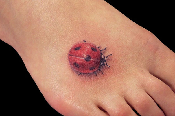 3D ladybird on foot tattoo