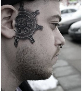A ship's wheel face tattoo