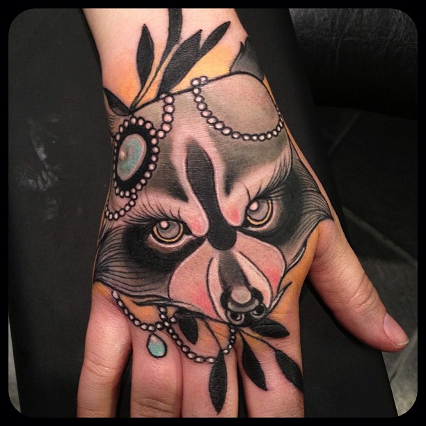 Amazing raccoon face hand tattoo