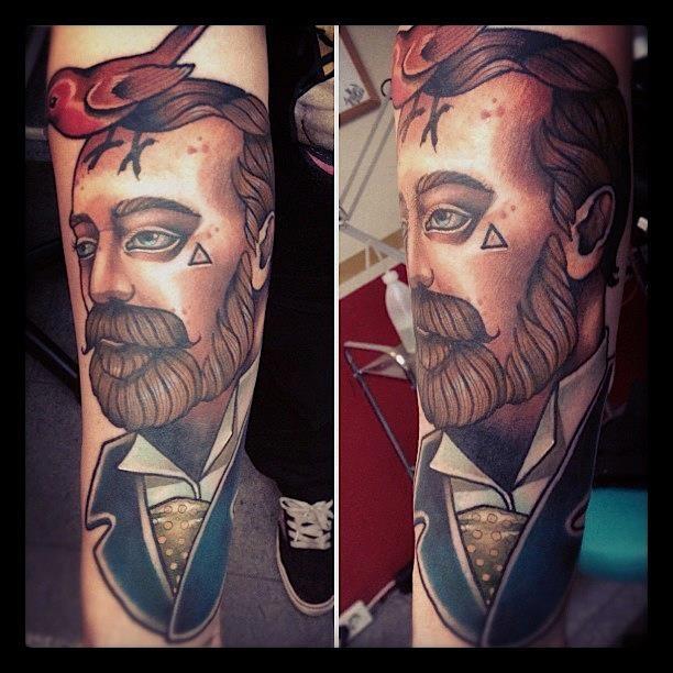 Bird on man's head tattoo by Alex Dorfler