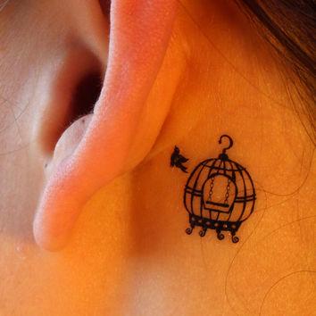 Birdcage behind ear tattoo