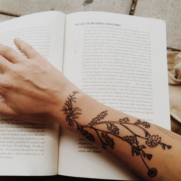Book and plants arm tattoo