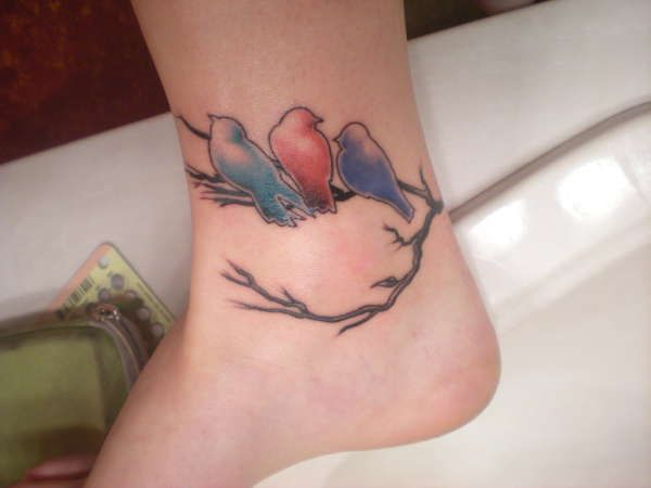 Colourful birds on a branch tattoo