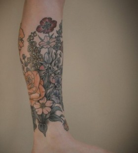 Colourful flowers leg tattoo by Kirsten Holliday