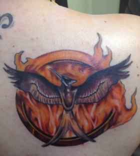 Cool flaming mockingjay back tattoo