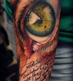 Eye and writing tattoo by Florian Karg