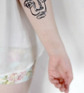 Face on arm like telephone tattoo
