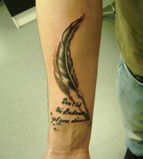 Feather pen and quote arm tattoo