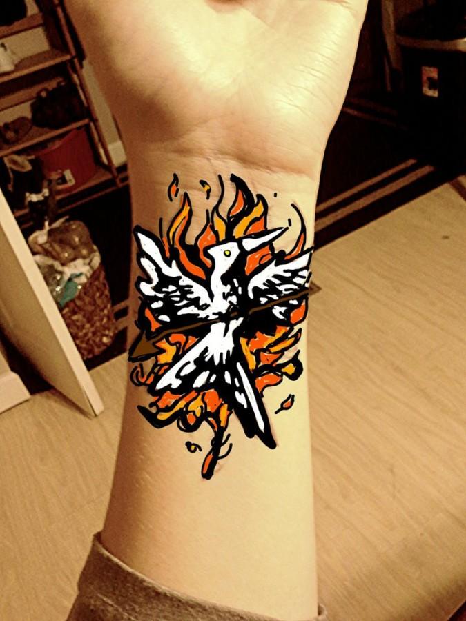 Flaming mockingjay wrist tattoo