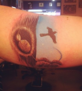 Flying mockingbird arm tattoo