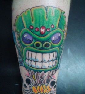 Green tiki and skulls tattoo