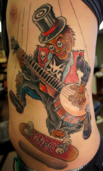 Guitar playing puppet tattoo