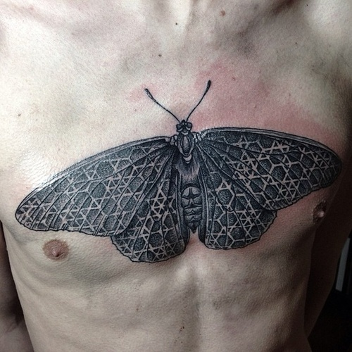 Large moth chest tattoo