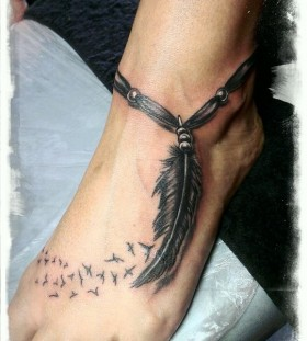Leg's feather and tribal bird tattoo