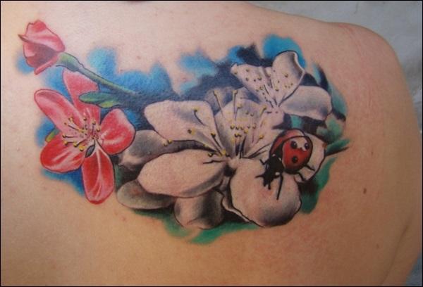Lovely ladybug and flowers tattoo
