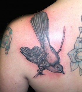 Mockingbird on a branch back tattoo