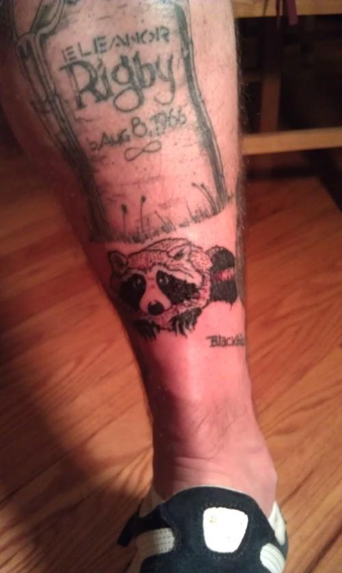 Raccoon and gravestone tattoo
