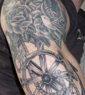 Roses and wheel arm tattoo