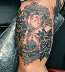 Sand clock and roses arm tattoo