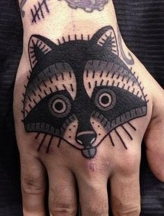 Simple raccoon face hand tattoo
