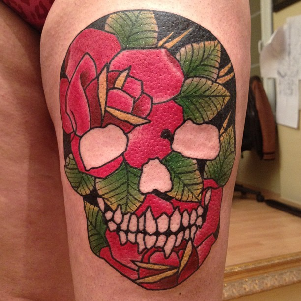 Skull and red flowers tattoo