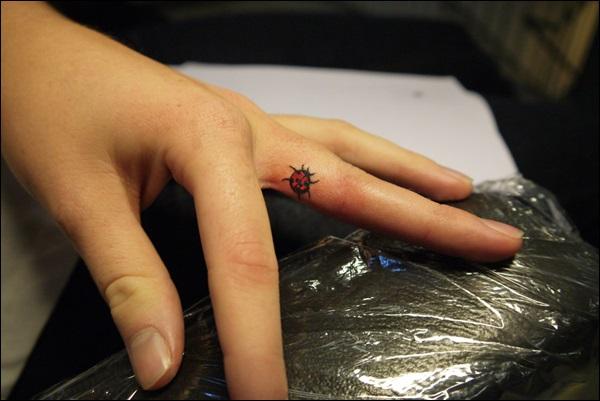 Small ladybug finger tattoo