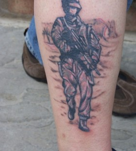 Soldier with gun leg tattoo