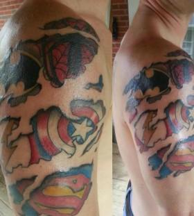 Superhero logos arm tattoo