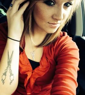 Blonde girl's scissor tattoo