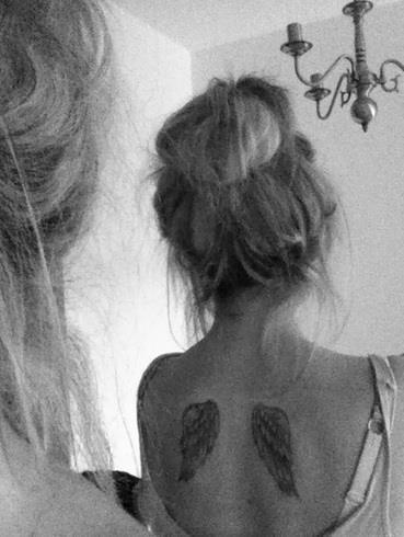 Back girl's wing tattoo