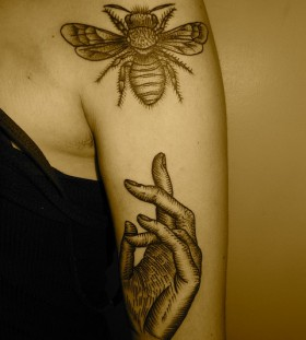 Black hand and bee tattoo on arm