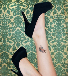 Black high-heel and bee tattoo on leg