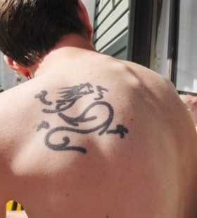 Black ornamentally men's back tattoo