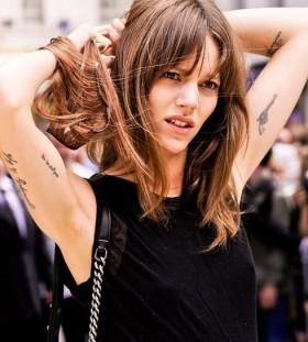 Black words and gun women's fashion style tattoo