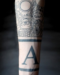 Eye and black letter men's arm tattoo