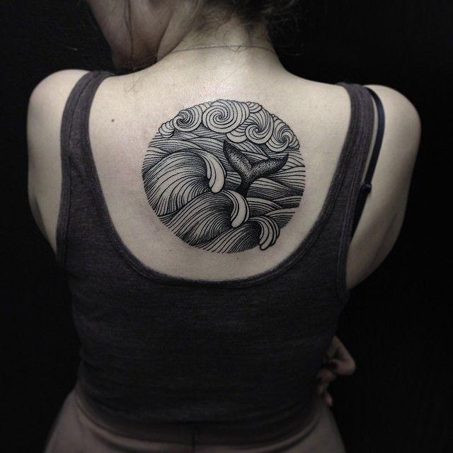 Girl's back whale tattoo