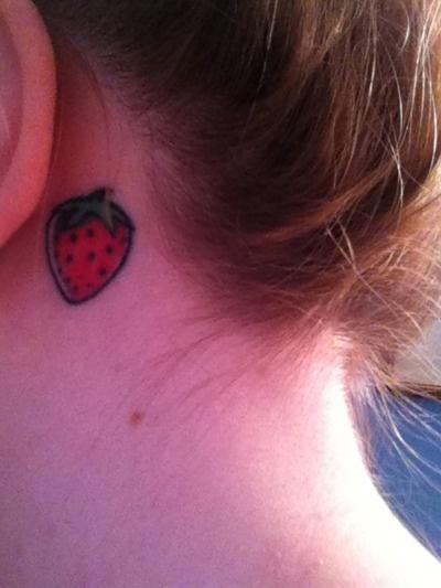 Girl's ear strawberry tattoo