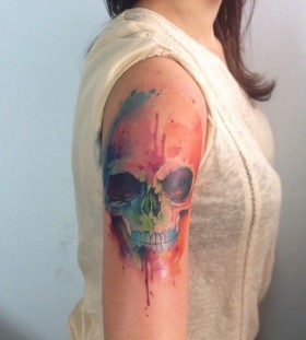 Girl's shoulder watercolor skull tattoo