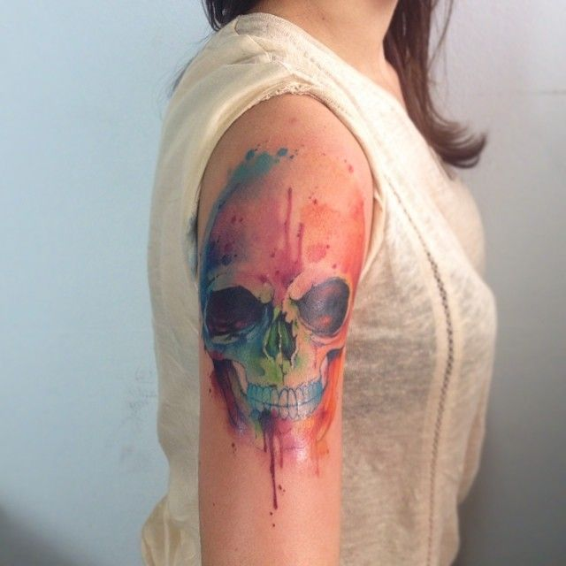 Girl's shoulder watercolor skull tattoo