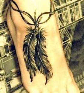 Leg's black feather tattoo