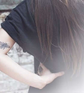 Long hair girl and bee tattoo on arm