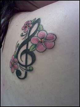 Lovely flower and black clarinet tattoo