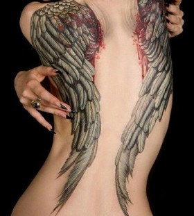 Naked women's angel tattoo