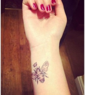 Red nails and bee tattoo on arm