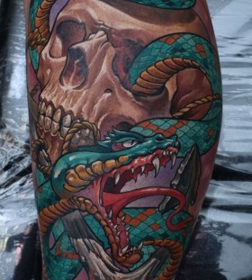 Skull and green snake tattoo on leg