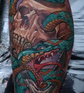 Skull and green snake tattoo on leg