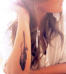 Women's arm's feather tattoo