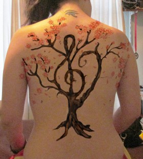 Women's back clarinet tattoo